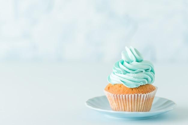Babeczka z błękitną kremową dekoracją na talerzu - błękitny pastelowy horyzontalny sztandar