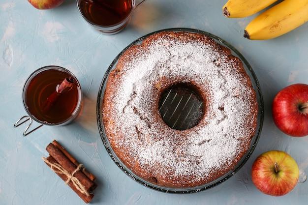 Babeczka z dziurą pośrodku z jabłkami, bananami i cynamonem, posypana cukrem pudrem na jasnoniebieskim tle