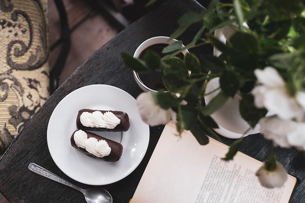 Babeczka z kawą i książką pod wazonem z różami w romantycznej kawiarni retro. mieszkanie leżeć