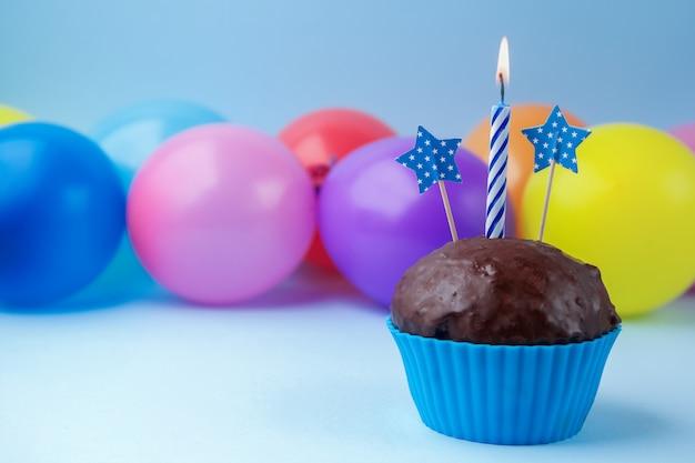 Babeczka z kolorową urodzinową świeczką i balonami