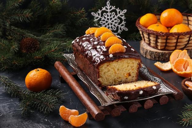 Babeczka z mandarynkami, oblana polewą czekoladową w nowy rok. świąteczna martwa natura.