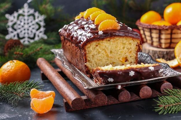 Babeczka z mandarynkami, pokryta polewą czekoladową, znajduje się na tle sylwestrowym