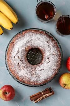 Babeczka z otworem pośrodku z jabłkami, bananami i cynamonem, posypana cukrem pudrem na jasnoniebieskiej powierzchni, dwie filiżanki herbaty, widok z góry