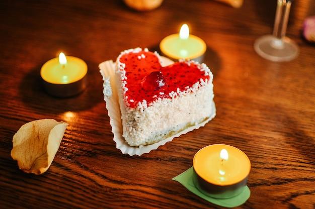 Babeczka z posypką i świecami w kształcie serca na drewnianym stole, kremowe ciasto truskawkowe, czerwona wiśnia na wierzchu. żółte liście suszonych róż. romantyczny tort, ciasto dla koncepcji walentynki. ścieśniać.