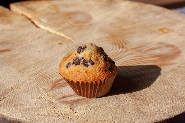 Babeczka z rodzynkami na drewnianym stojaku w słońcu. domowe wypieki. selektywne skupienie się na ciastku. poziomy.