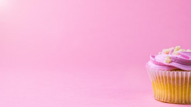 Babeczka z różowym kremem na jednolitej różowej powierzchni