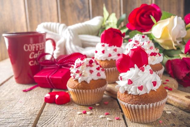 Babeczka z sercem na walentynki. walentynkowy słodki deser, babeczki waniliowe z bitą śmietaną waniliową i dekoracje z czerwonych serc cukrowych na walentynki, drewniany stół z bukietem różanych kwiatów