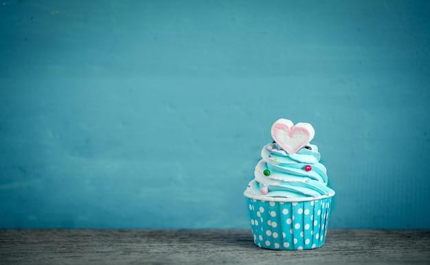 Babeczka z słodkim kierowym kształtem marshmallow przeciw błękitnemu tłu