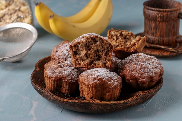 Babeczki bananowe z płatkami owsianymi posypane cukrem pudrem na talerzu kokosowym