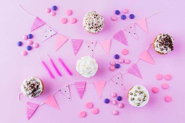 Babeczki; cukierki; świece i trznadel na różowym tle
