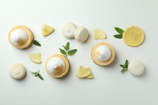 Babeczki cytrynowe, makaroniki i składniki na białym tle