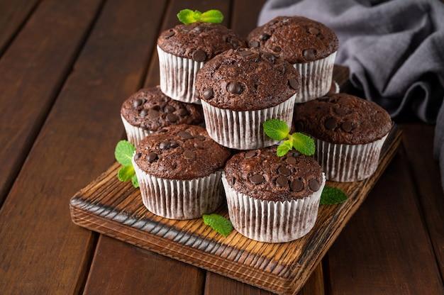 Babeczki czekoladowe lub babeczki z kroplami czekolady, świeżymi jagodami i miętą.