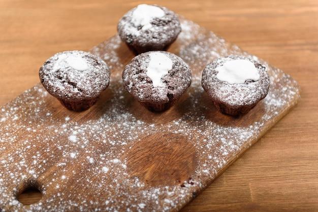 Babeczki czekoladowe z białym lukrem leżące na desce posypane cukrem pudrem