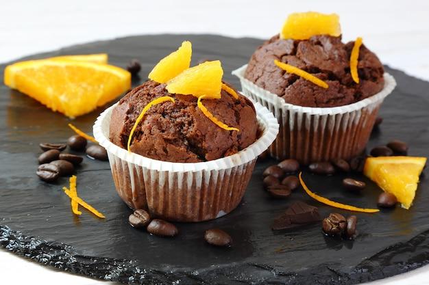 Babeczki czekoladowe z pomarańczami na czarnej tacy, selektywne skupienie