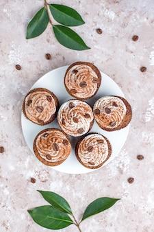 Babeczki do kawy ozdobione bitą śmietaną i ziarnami kawy.