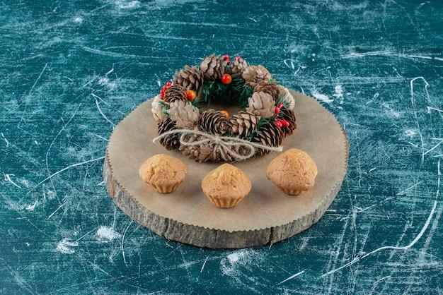Babeczki i sosnowy wieniec ułożone na drewnianej desce na niebiesko.