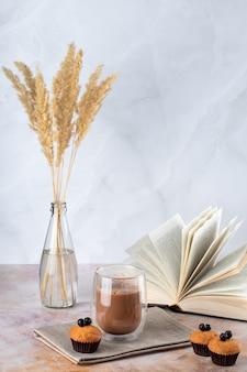 Babeczki i szklanka kawy z mlekiem na stole z książką i suchymi liśćmi na białym marmurowym tle