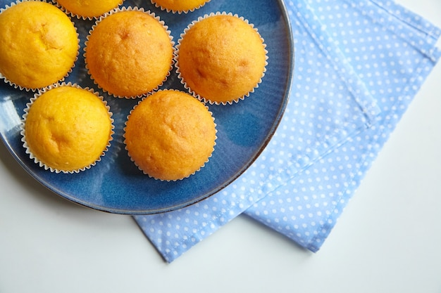 Babeczki na niebieskim talerzu na stole z serwetką