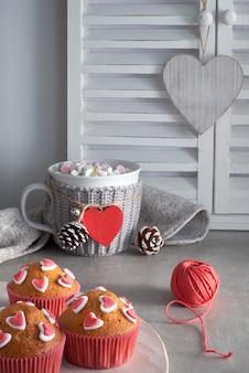 Babeczki ozdobione cukrowymi sercami i filiżanką z czerwonym sercem na jasnoszarej ścianie
