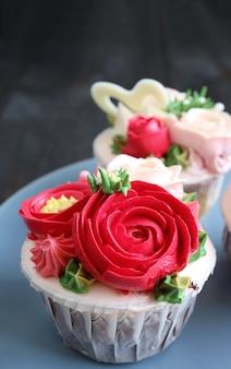 Babeczki ozdobione lukrem w kształcie czerwonych kwiatków na bladoniebieskim talerzu