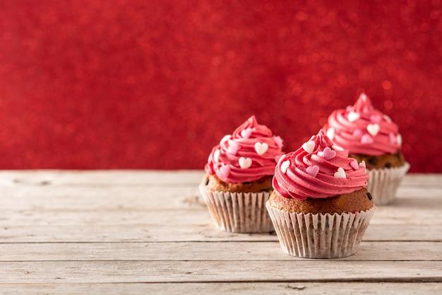 Babeczki ozdobione serduszkami z cukru na walentynki na drewnianym stole i czerwonym tle
