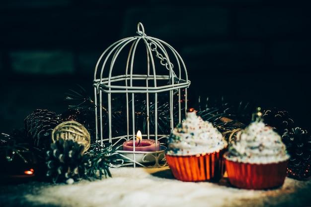 Babeczki, świeca bożonarodzeniowa i ozdoby świąteczne na drewnianym tle .zdjęcie z miejscem na kopię