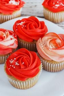 Babeczki waniliowe ozdobione czerwoną różą z kremu na białym tle