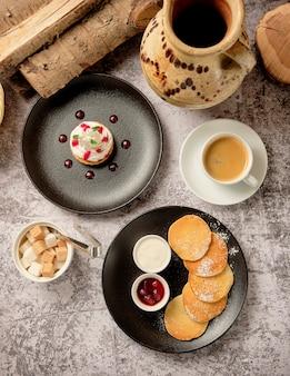 Babeczki z bitą białą waniliową śmietaną z naleśnikami i dżemem jagodowym, filiżanka americano na czarną kawę na śniadanie