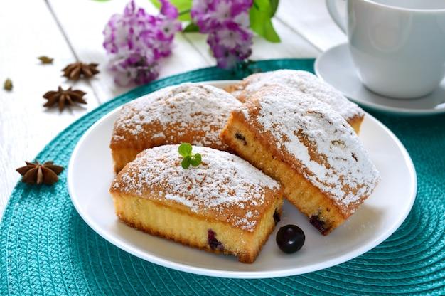 Babeczki z jagodami i cukierem pudrem na talerzu na białym drewnianym stole. prostokątne babeczki i herbata