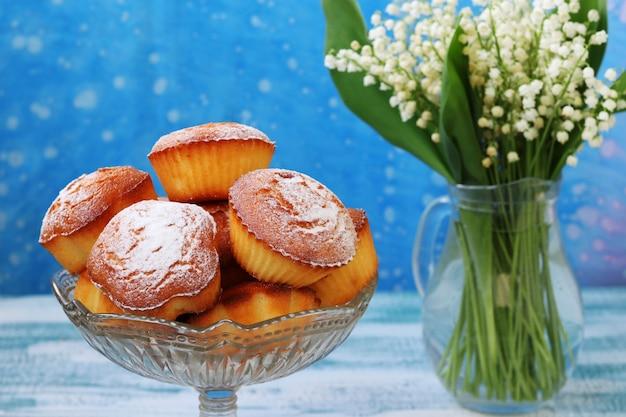 Babeczki z kaszą manną na kefirze w przezroczystym wazonie na niebieskim tle. w pobliżu jest dzban z konwaliami