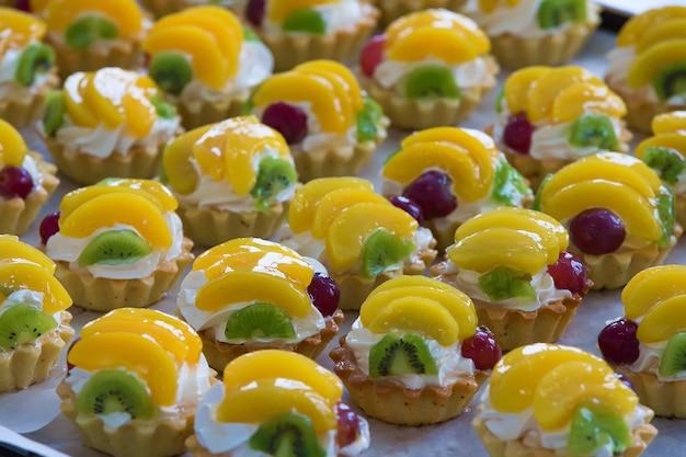 Babeczki z kremem i owocami. babeczki z kremem i owocami brzoskwiniowymi kiwi i wiśniami. dużo pieczenia