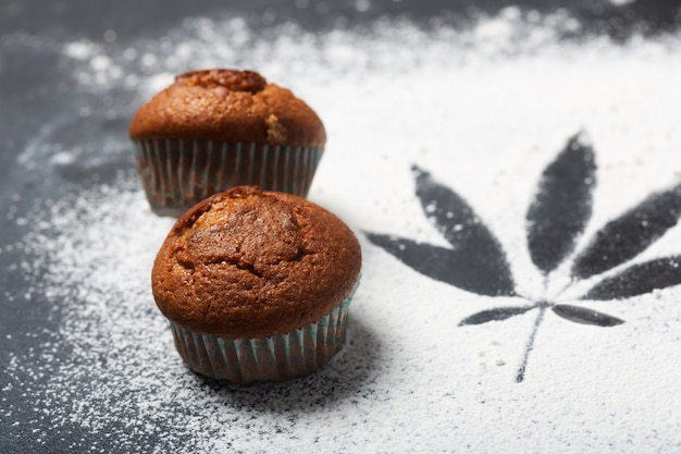 Babeczki z marihuaną na stole, ciemne tło. cdb karmowy pojęcie, zamyka w górę strzału