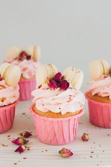 Babeczki z różową śmietaną, makaronikami i różami