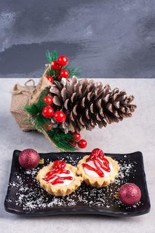 Babeczki z sosem truskawkowym na czarnym talerzu, otoczone świątecznymi ozdobami na marmurowej powierzchni