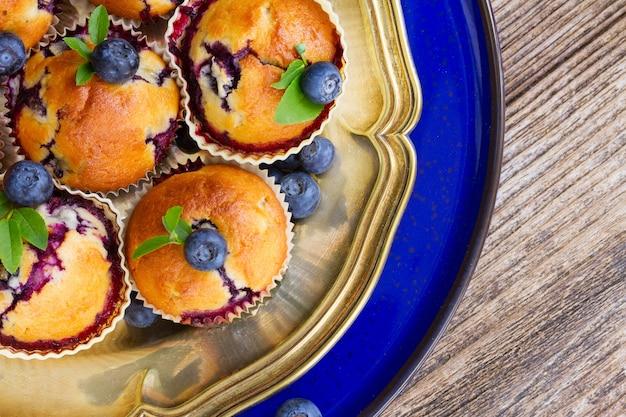 Babeczki ze świeżymi jagodami i liśćmi na srebrnym i niebieskim talerzu