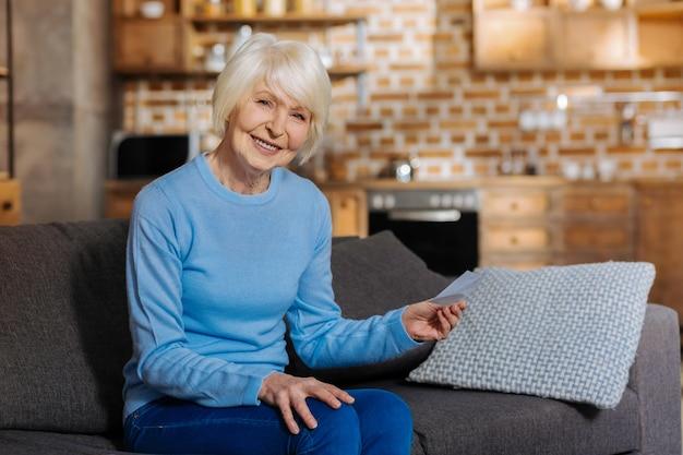 Baby boomer. zachwycona miła starsza kobieta trzymająca karteczkę i uśmiechnięta będąc w dobrym nastroju