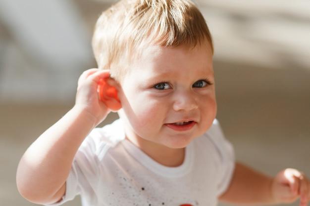 Baby boy słucha, by przyłożyć rękę do ucha.