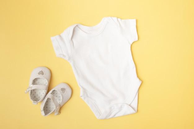 Baby clobodysuit makieta na żółtym tle dla miejsca tekstu lub logo