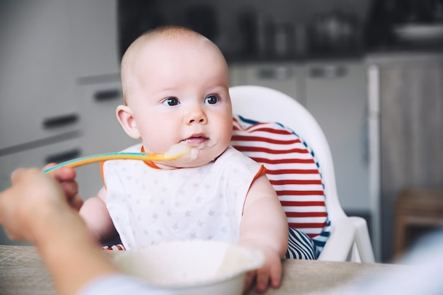 Babys pierwszy pokarm stały matka karmi małe dziecko łyżką puree codzienna rutyna przekąski