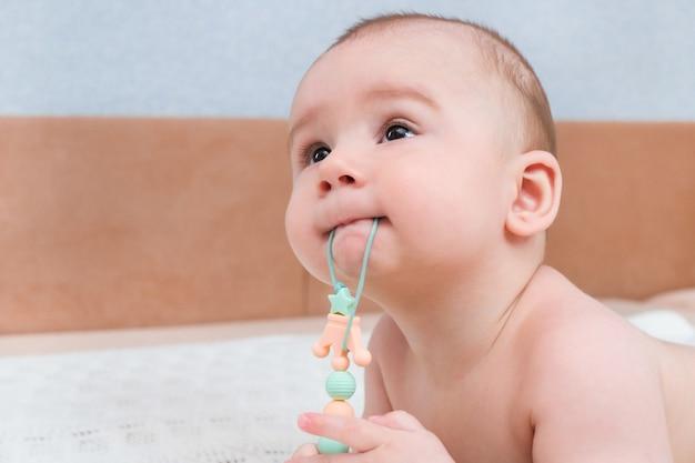 Babys wyrzynają się mleczne zęby, swędzą dziąsła. dzieciak ma w ustach zabawkę