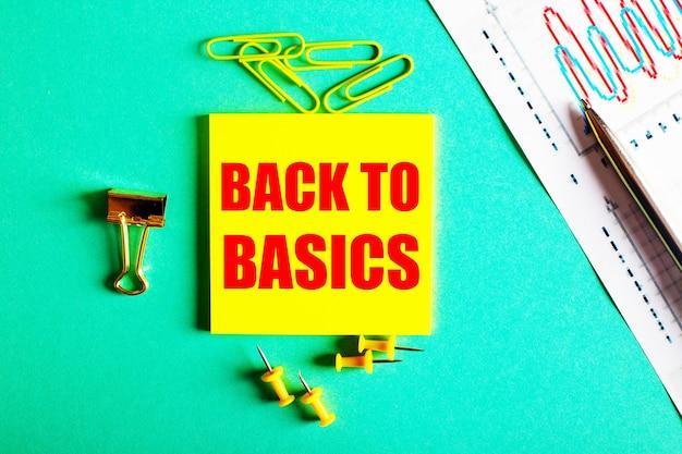 Back to basics jest napisane na czerwono na żółtej naklejce na zielonej powierzchni w pobliżu wykresu i ołówka