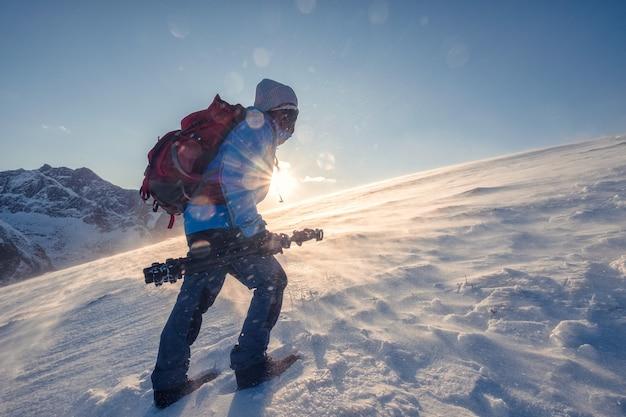 Backpacker człowiek alpinizm na śniegu góry z promieniem słońca w zamieci w norwegii