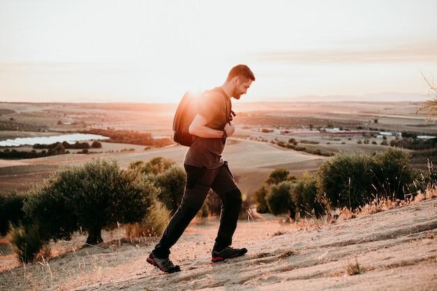 Backpacker człowiek piesze wycieczki w szczyt góry o zachodzie słońca, podziwiając krajobraz. natura i styl życia