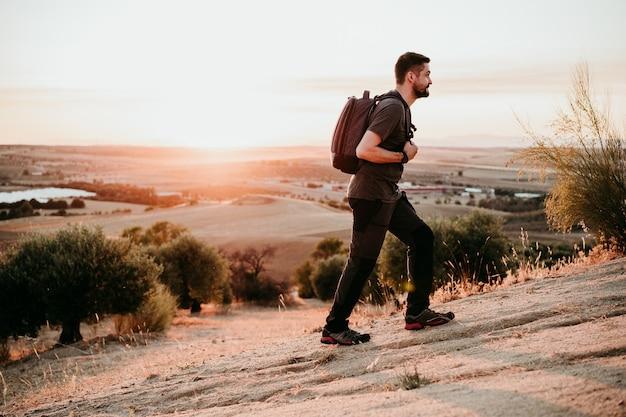Backpacker człowiek piesze wycieczki w szczyt góry o zachodzie słońca, podziwiając krajobraz. styl życia i natura