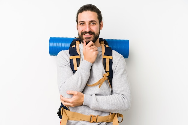 Backpacker młody człowiek uśmiecha się szczęśliwy i pewny siebie, dotykając podbródka ręką