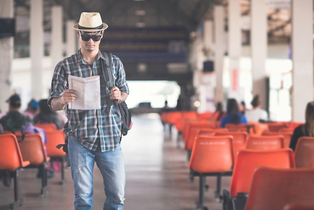 Backpacker trzyma mapę na stacji thetrain z podróżnikiem