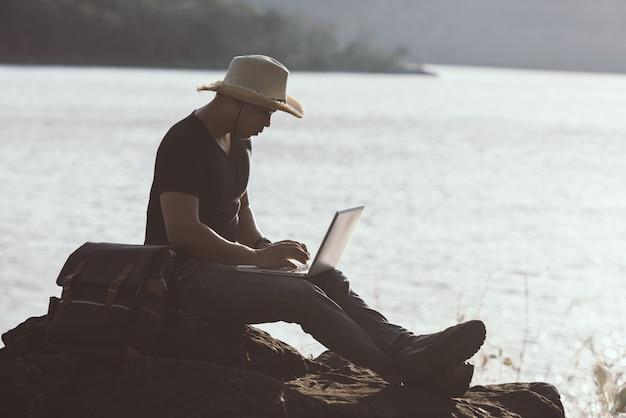 Backpacker zrelaksować się w górach za pomocą laptopa