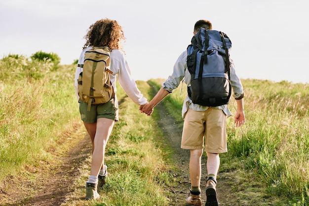 Backpackers chodzą po wiejskiej drodze