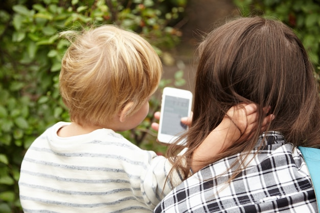 Backside portret matki i syna na zewnątrz. blond włosy małego chłopca kontrastują z brązowymi włosami kobiety. dwie osoby patrzące z zainteresowaniem na smartfona, dzieciak przytulający kobietę na szyi.