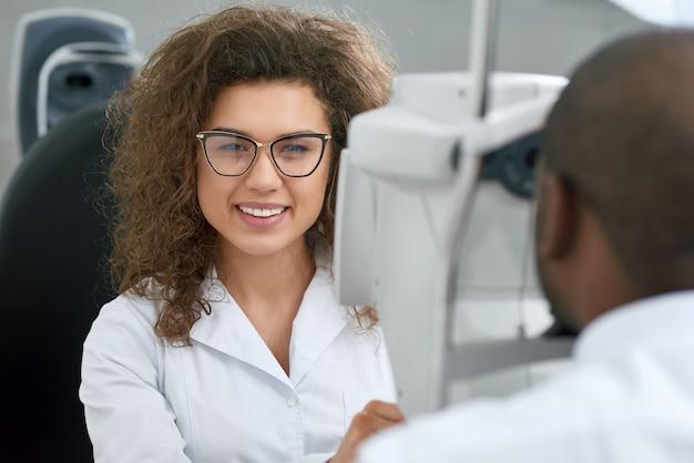 Backview młodego człowieka siedzi podczas sprawdzania wzroku z wykwalifikowaną okulistą.
